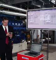 Maxim Burtovy of the energy services company Energy Alliance demonstrates equipment at a Ukrainian glassware plant. USAID photo.
