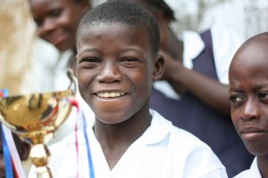 A Mango Town student holds the trophy the school won in a government-sponsored spelling bee. Photo by Timothy Spence