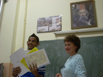 On graduation day, Stefan Radu displays his diploma and a handful of honors certificates. Standing next to him is teacher Anica Bacic.