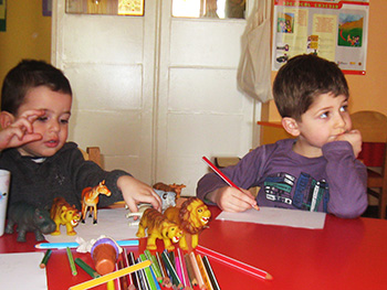 Kakhi Chanukvadze, right, and a classmate choose animals to paint at their Tbilisi preschool. Photo by Tamar Kikacheishvili.