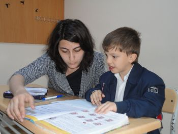 Shahin Bashirli gets help with his school work from Elnura Rzayeva. Photo by Arifa Kazimova.