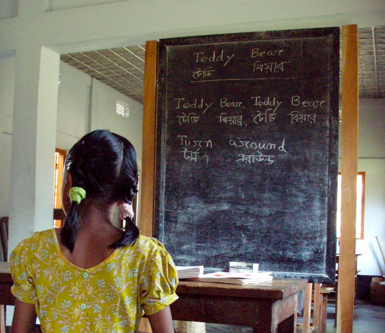 A girl in a yellow dress sits at her desk in a Bengali school. By Fionn Kidney, Flickr.